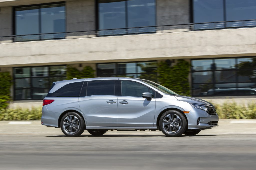 A silver 2021 Honda Odyssey driving down a city street