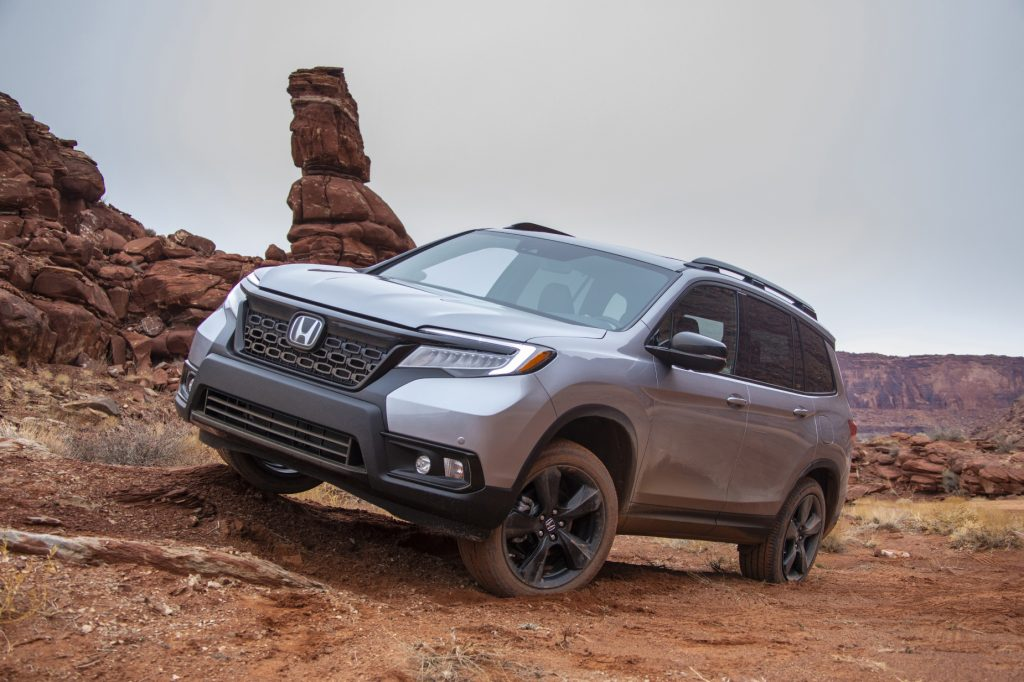 A silver 2021 Honda Passport driving over rugged terrain