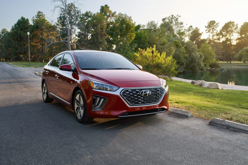 A red 2020 Hyundai Ioniq Hybrid parked on display with trees in the background