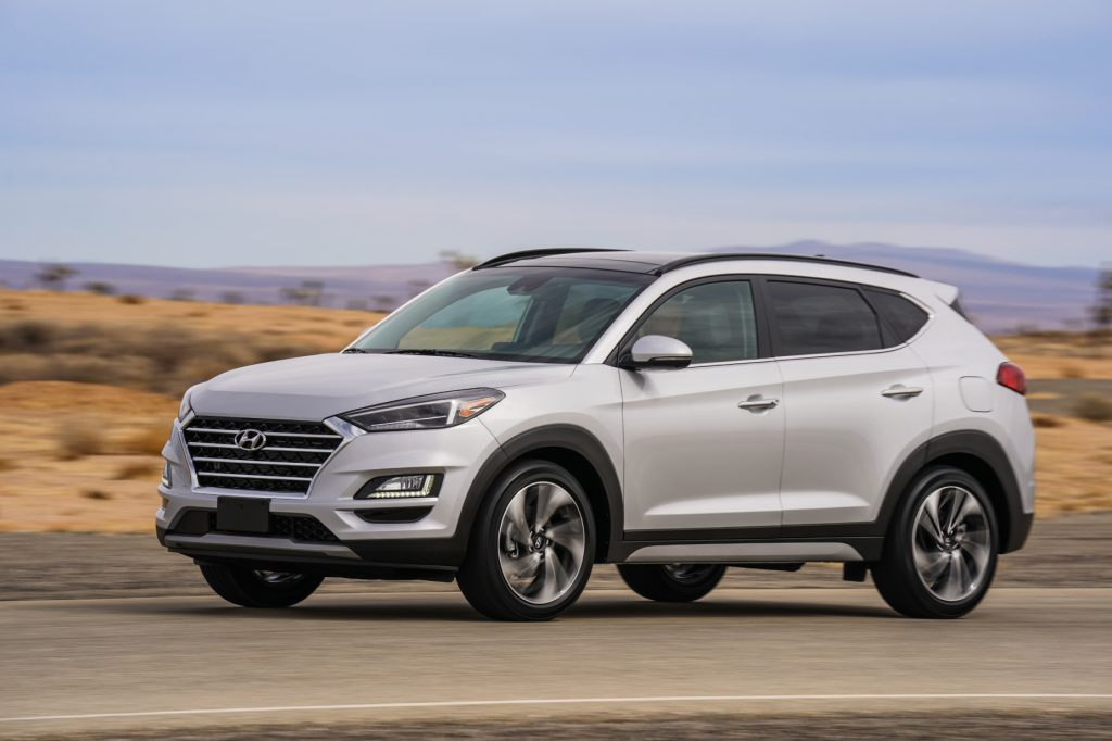 A silver 2021 Hyundai Tucson parked on display next to rugged terrain