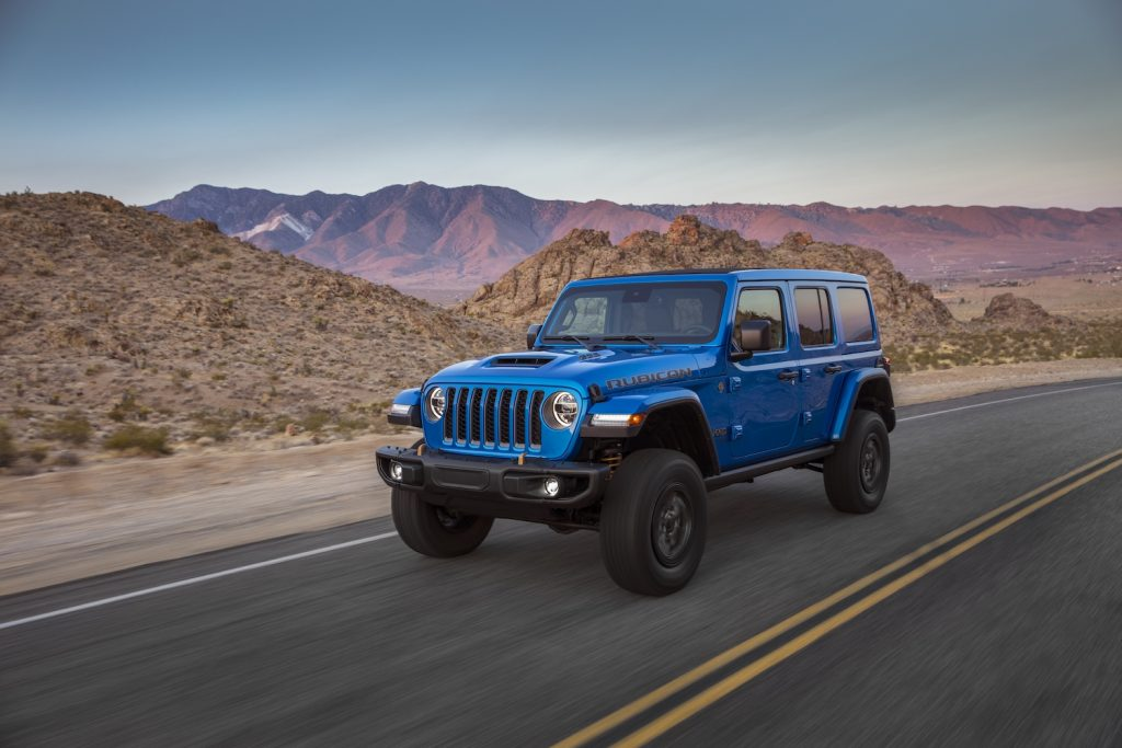2021 Jeep Wrangler driving with a mountain range in the background