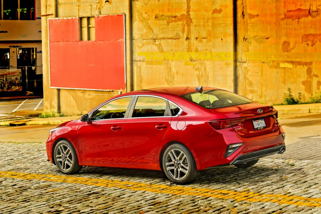 A red 2021 Kia Forte packed next to a colorful wall