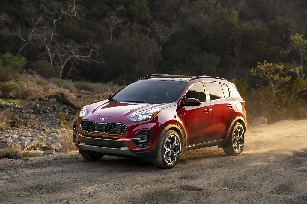 A dark-red 2021 Kia Sportage crossover SUV drives on a dusty road