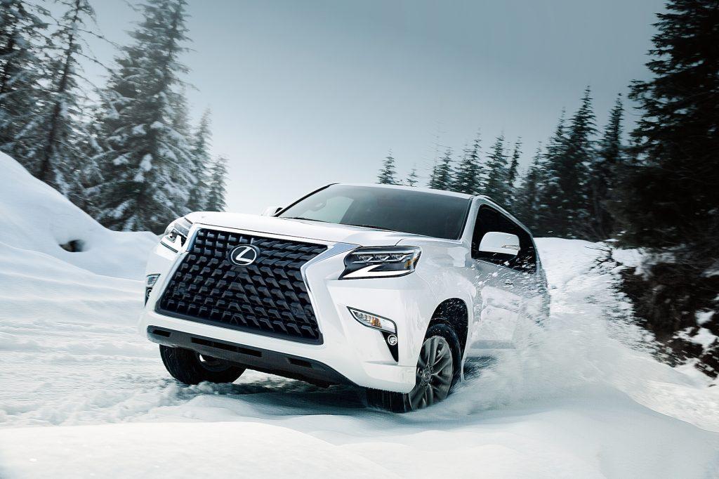 A white 2021 Lexus GX full-size SUV drives through the snow