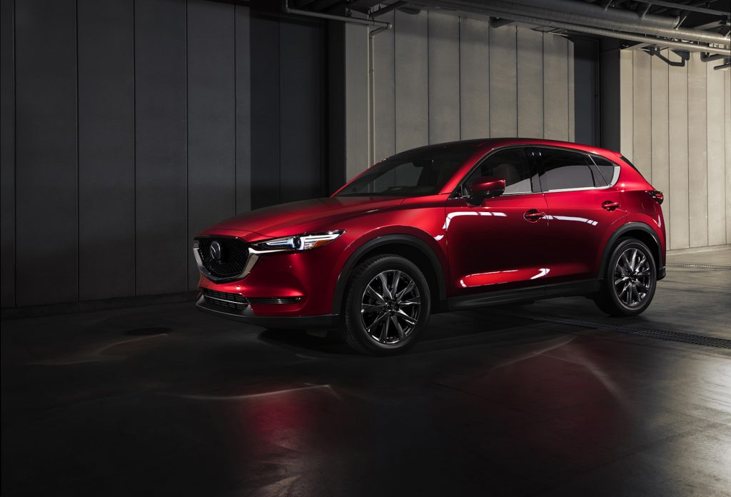 A metallic red 2021 Mazda CX-5 is parked next to a gray concrete building