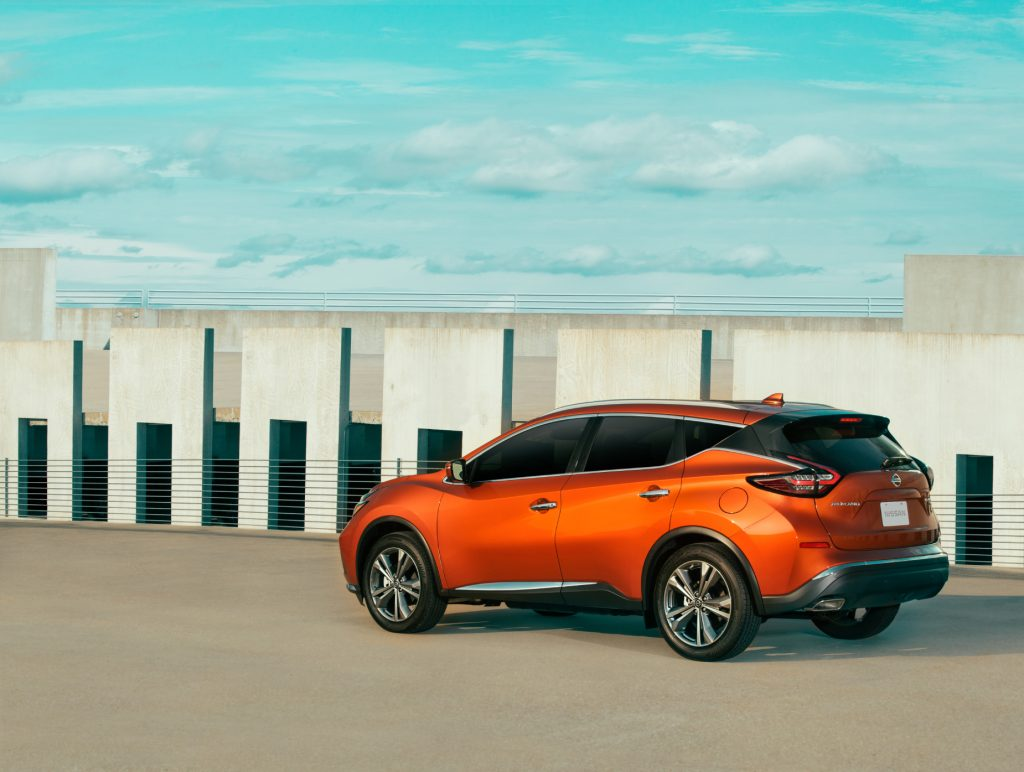An orange 2021 Nissan Murano parked on display next to a wall with a blue sky in the background
