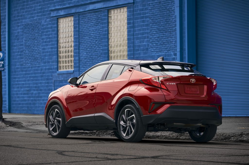 A red 2021 Toyota C-HR parked in front of a blue building