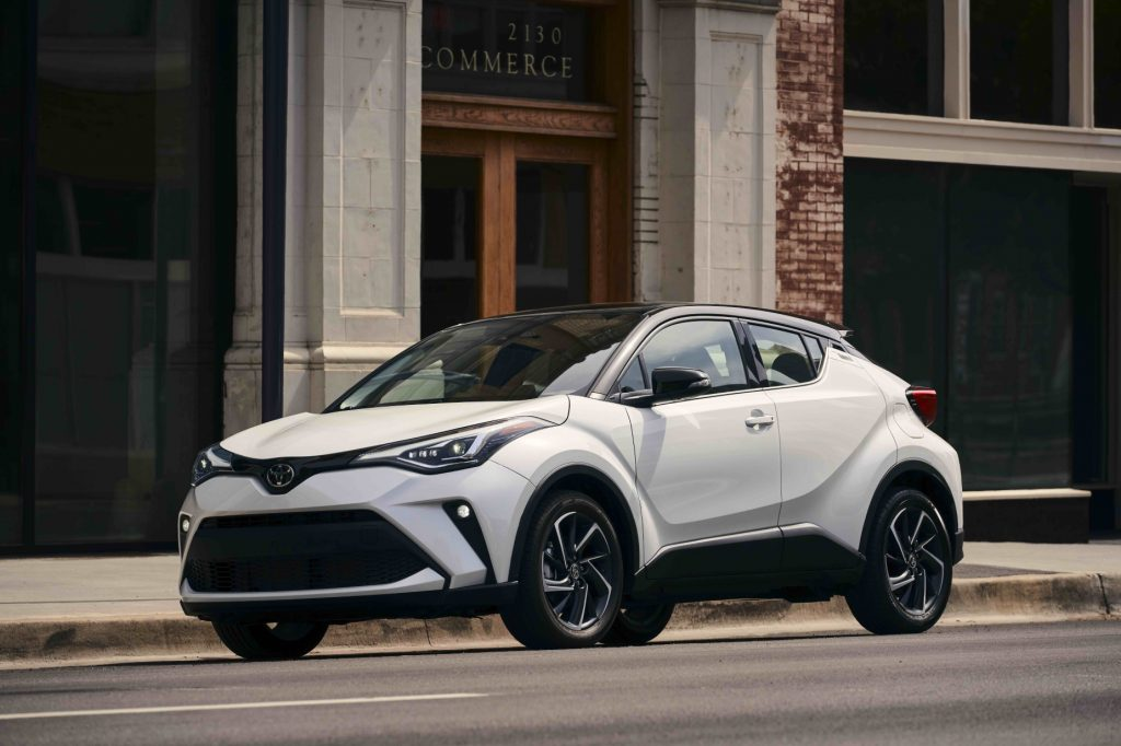A white 2021 Toyota C-HR driving down a city road