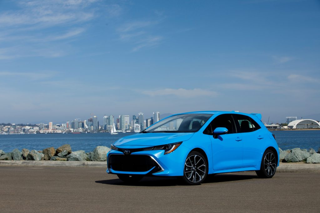 A blue 2021 Toyota Corolla Hatchback on display next to the water