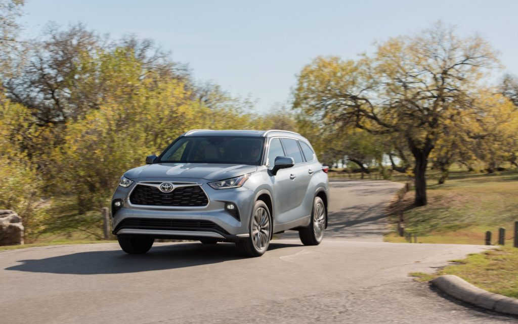 A silver 2021 Toyota Highlander parked between two trees