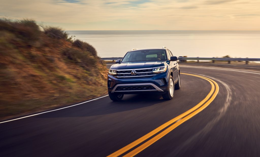 A blue 2021 Volkswagen Atlas driving down a highway road