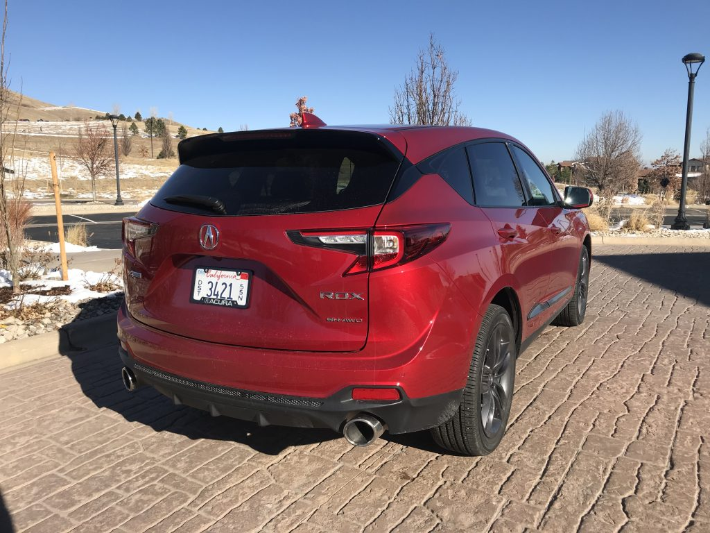 A red Acura RDX parked curbside.