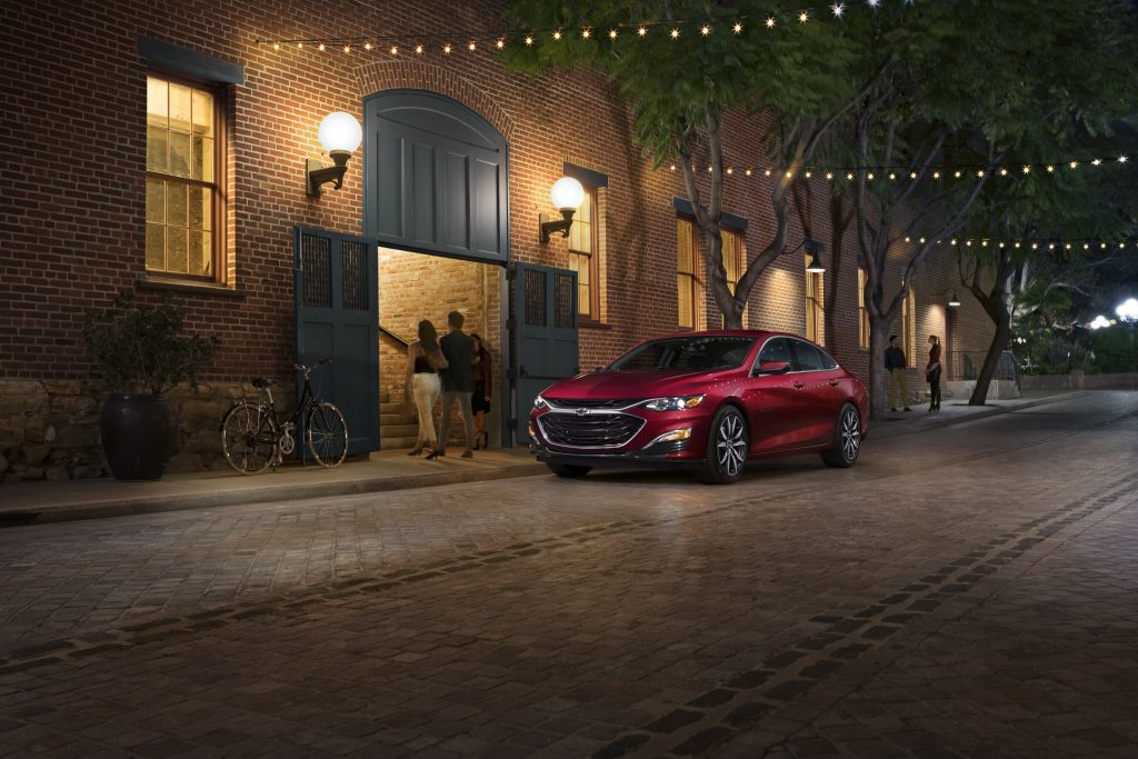 A red 2021 Chevy Malibu on display next to a building with lights on it