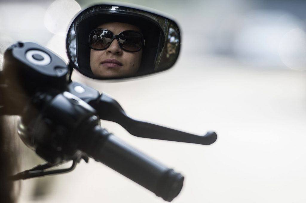 A female motorcycle rider reflected in one of her Harley-Davidson mirrors