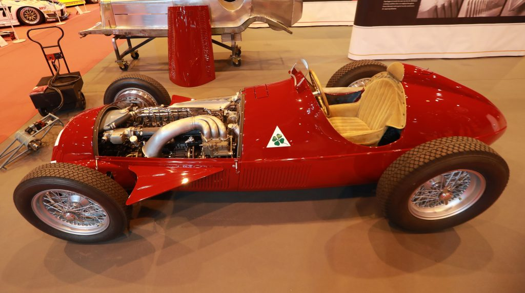 A red, center-drive, Alfa Romeo racecar from the 1930s