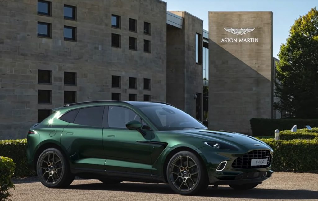 An Aston Martin DBX sits in front of a Aston Martin building