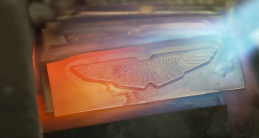 The Aston Martin wing badge undergoes heating from a torch.