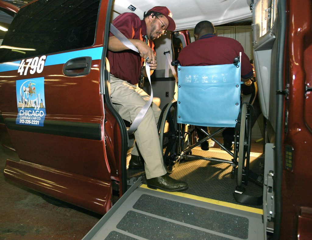 Chicago Carriage Cab taxi cab drivers William Bundy (L) and Rafiu Ayantoye use a ramp to load a wheelchair client