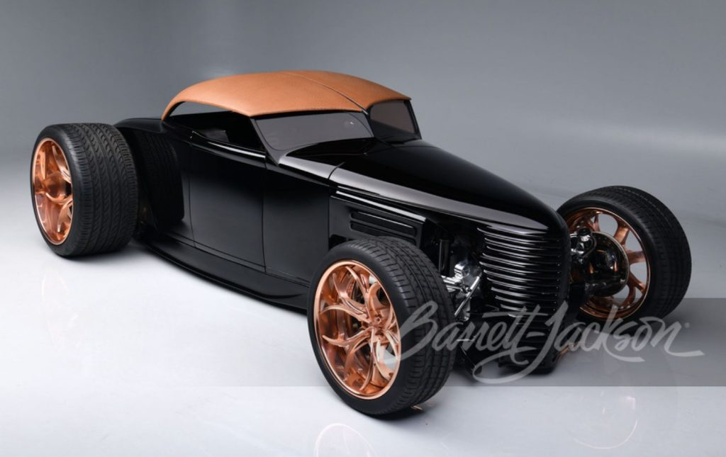 The front quarter of a black custom rat rod sits on copper finished, one-off wheels.