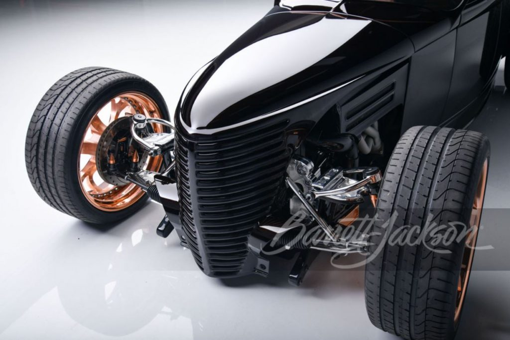 The front end of a black custom rat rod sits on copper finished, one-off wheels.