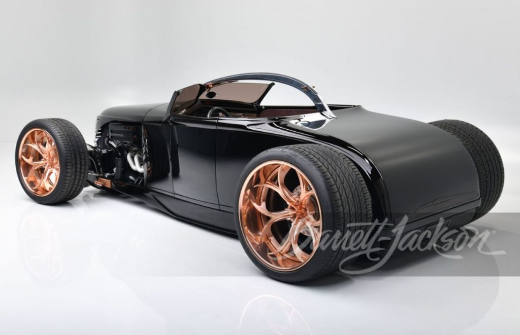 The rear of a black custom rat rod sits on copper finished, one-off wheels.