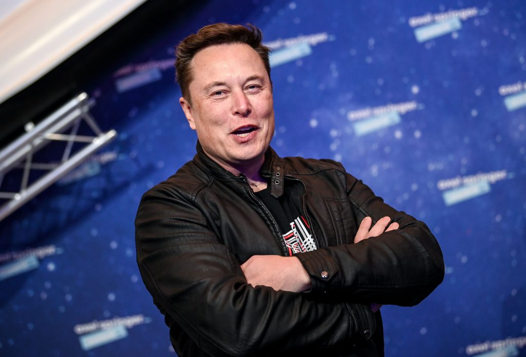 Elon Musk smiles for a photo on the red carpet
