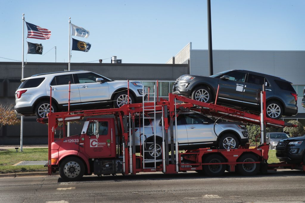 A truck carrying Ford SUVs to a car sales dealership