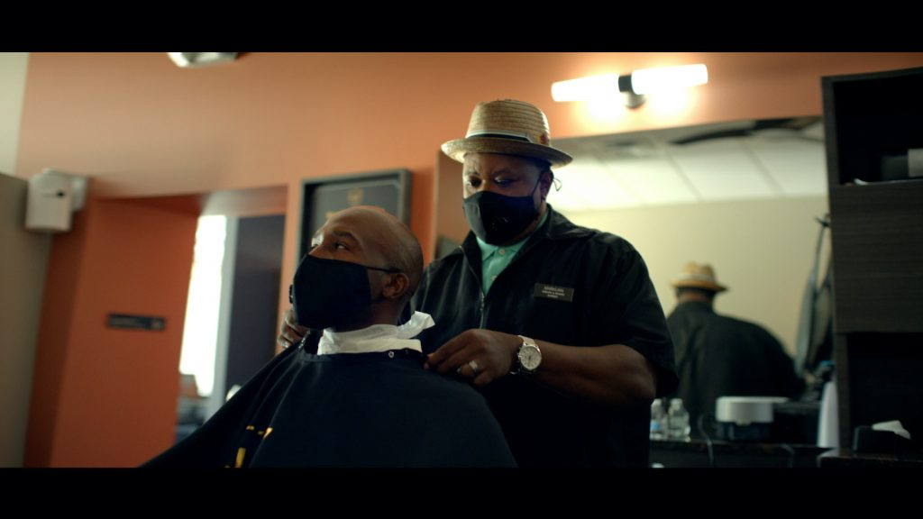 Two men wearing masks at the barber