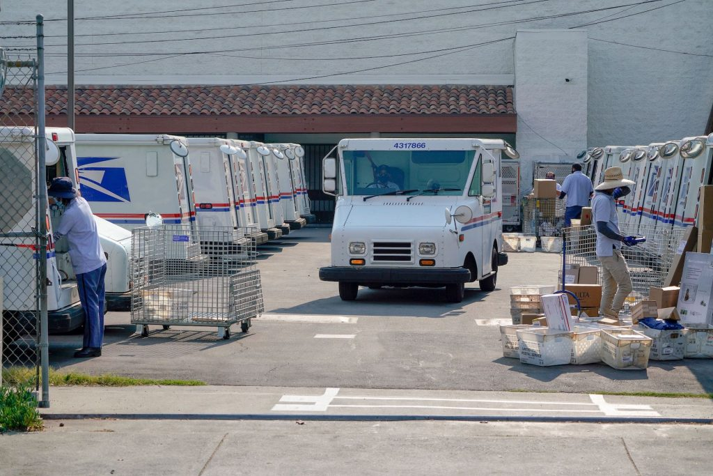 An image take just outside of a USPS dispatch center where trucks and workers are loading packages.