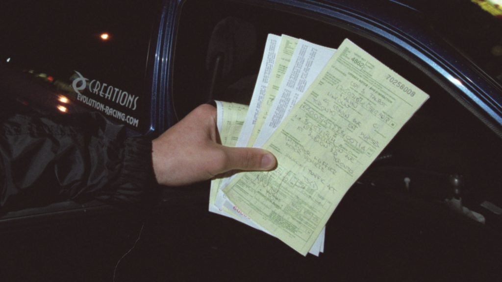 An image of a few speeding tickets held up for the camera to see.