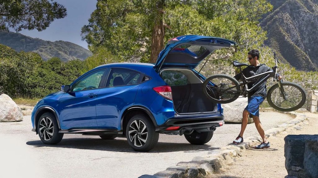 A man loading a bike into a blue 2021 Honda HR-V with the trunk open.