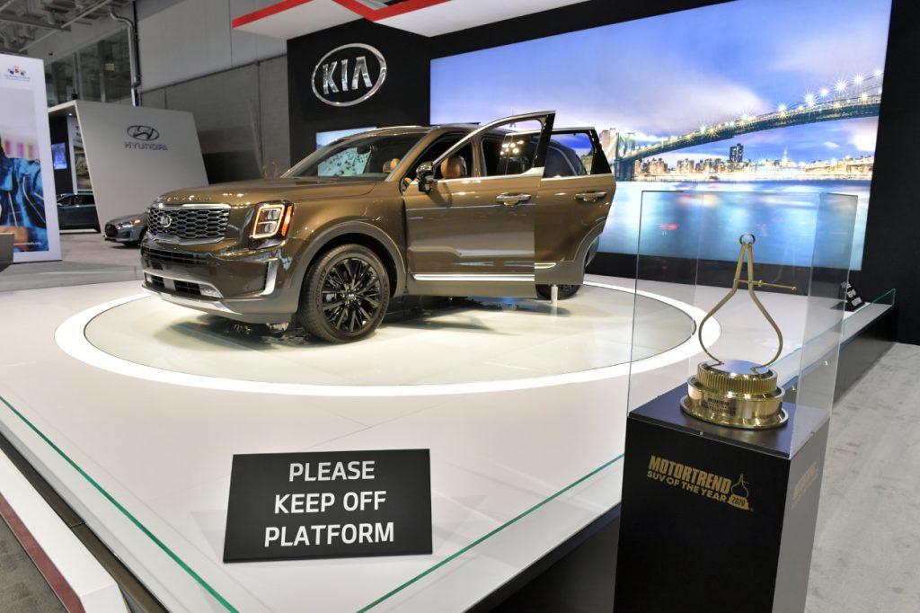 A Kia Telluride on display next to an award