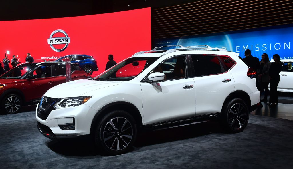 A white Nissan Rogue on display at an auto show