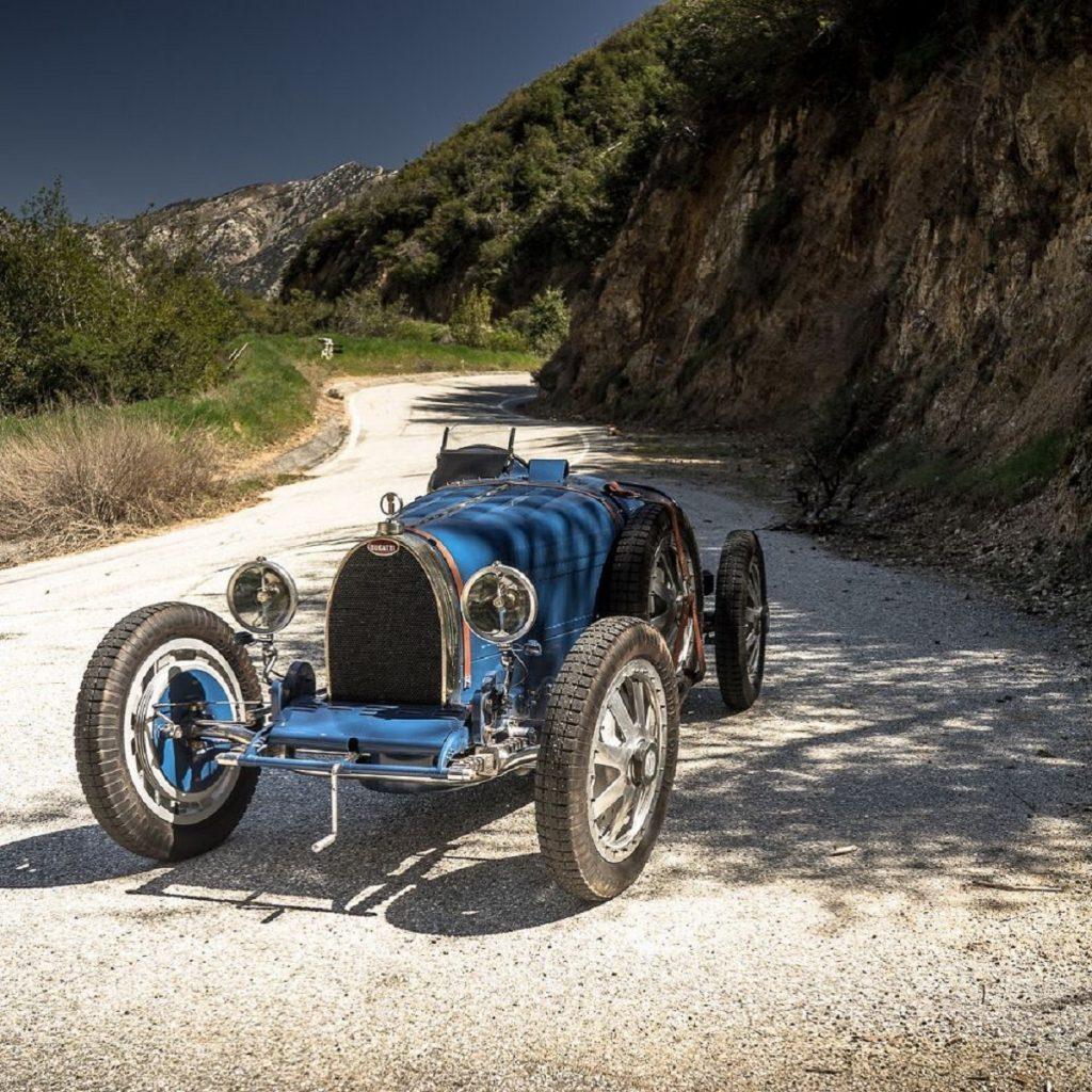 A blue Pur Sang Bugatti Type 35 replica on a rocky trail