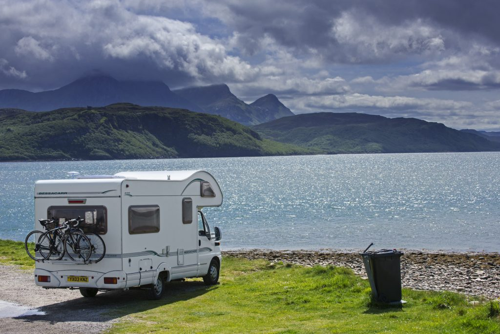 An RV camper parked on the shore along Kyle of Tongue, shallow sea loch in northwest Highland, Sutherland, Scottish Highlands, Scotland, UK.