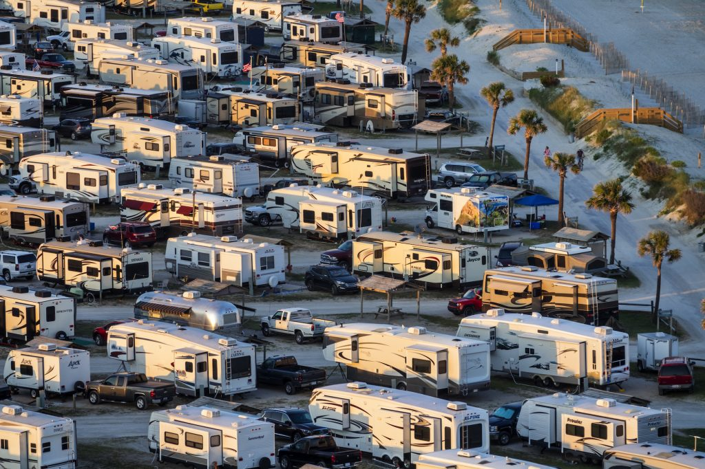 Motorhome and travel trailer RVs parked in Myrtle Beach Travel Park in South Carolina near sunset.