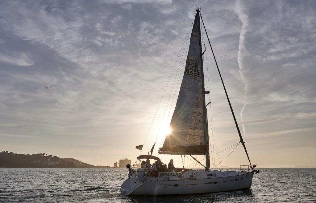 The sun sets behind a sailboat belonging to Escola de Navegação Treino de Mar (Navigation Training School of the Sea)