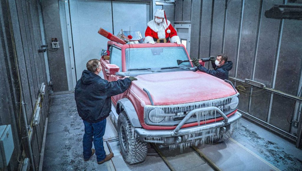 Santa stands in the back of the 2021 Ford Bronco's discussing cold weather testing results with two engineers | Ford Motor Company
