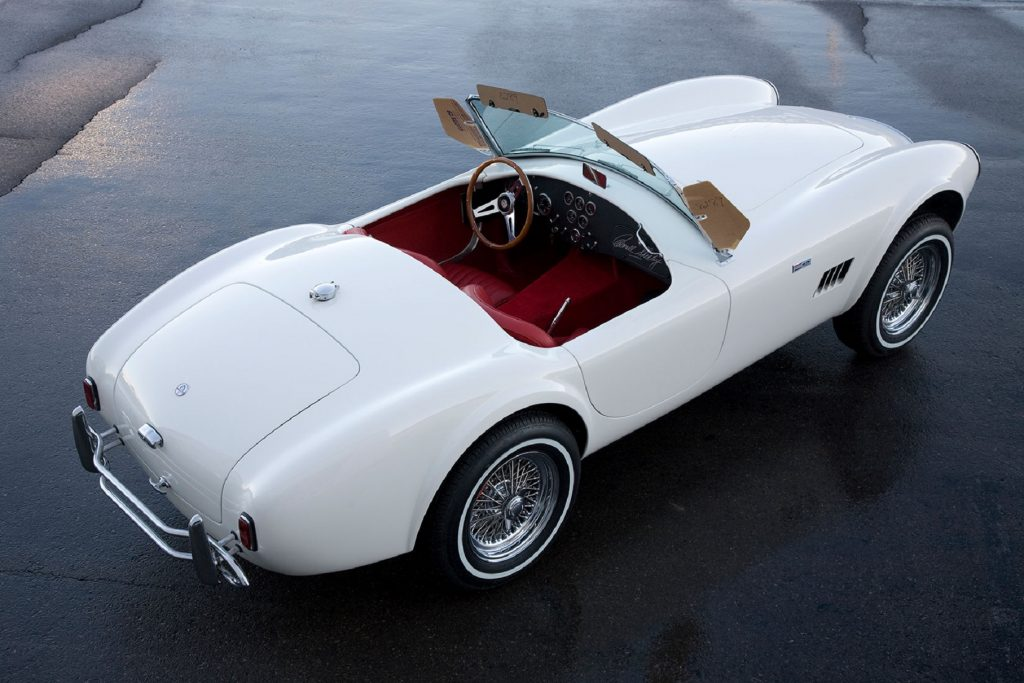 The overhead rear 3/4 view of a white Shelby Cobra 289 'Street Cobra' with a red interior