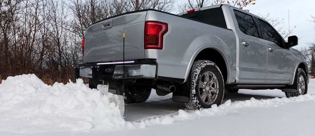A rear hitch mounted snowplow is attached to a silver Ford F-150