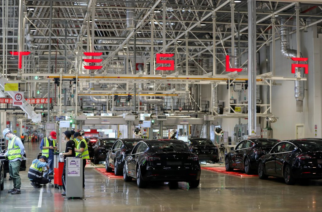 Employees working at a Tesla factory assembling cars