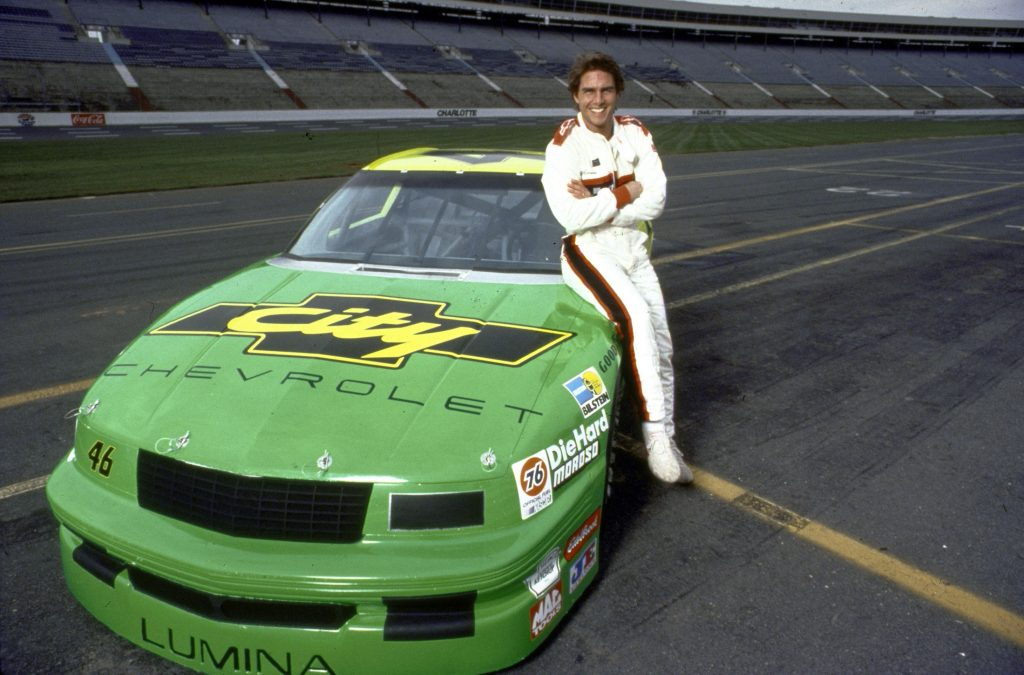 Tom Cruise leans on the lime green number 46 Chevrolet City Lumina.