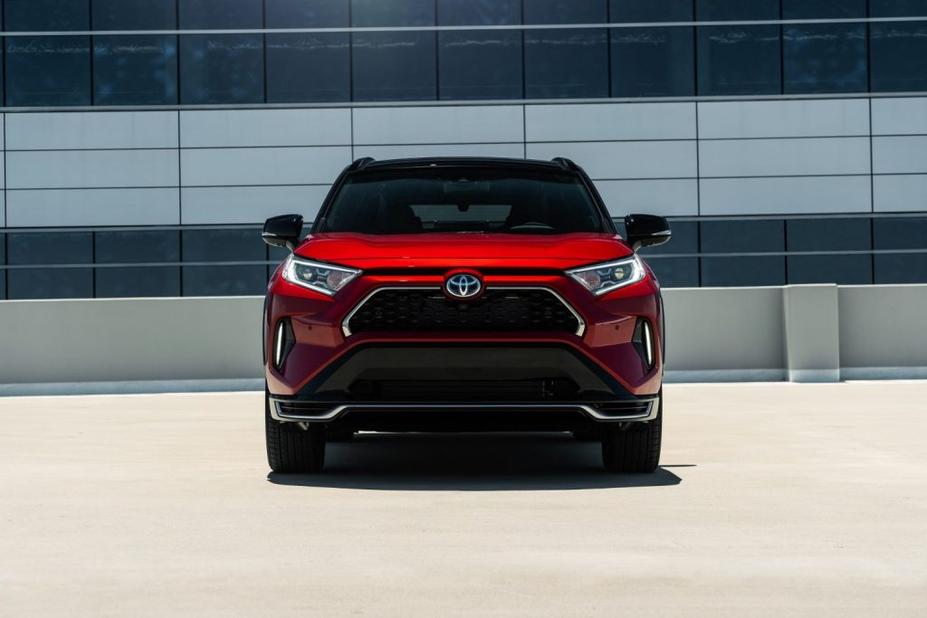 A red 2021 Toyota RAV4 Prime parked on the top of a parking deck.