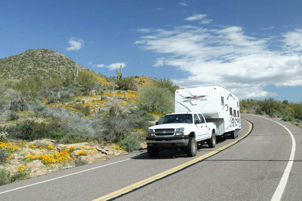A pickup tows a fifth-wheel RV trailer around a bend in the road.