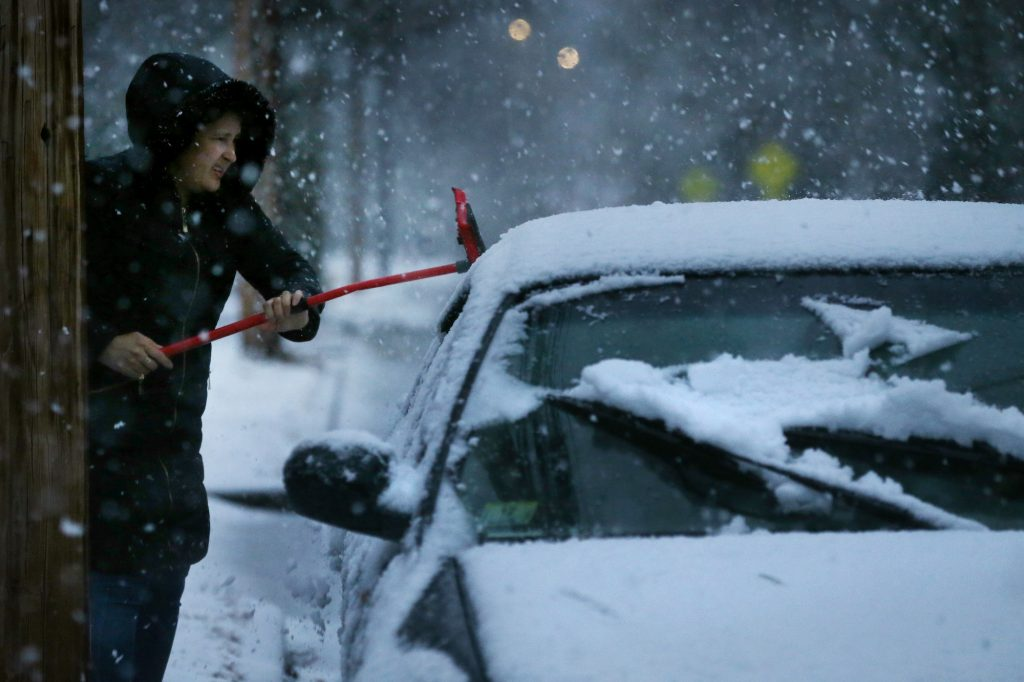 A woman clears snow from her car during a storm in Newton, MA, on December 05, 2020.