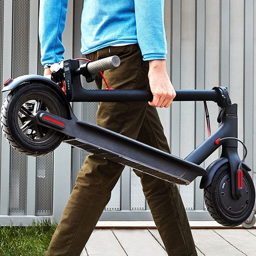 A man carrying a Xiaomi Scooter