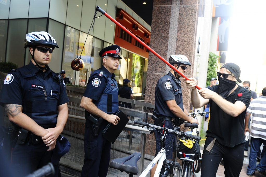 protester dangling donut in front of cop