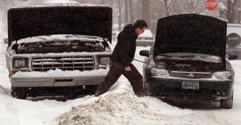 man jumping a car battery in the snow