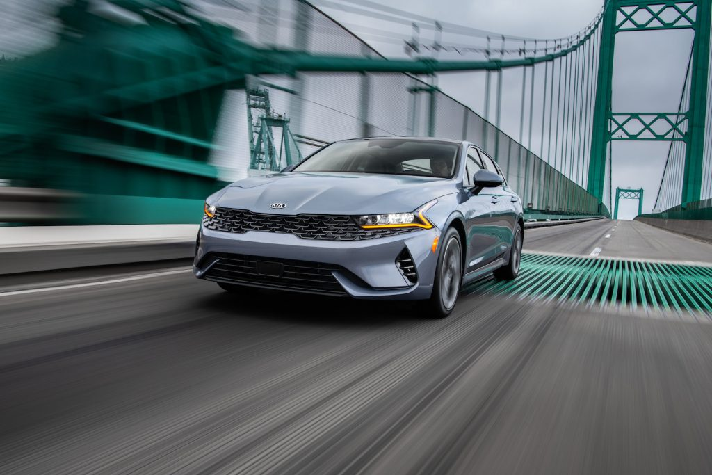 2021 Kia K5 driving across a bridge