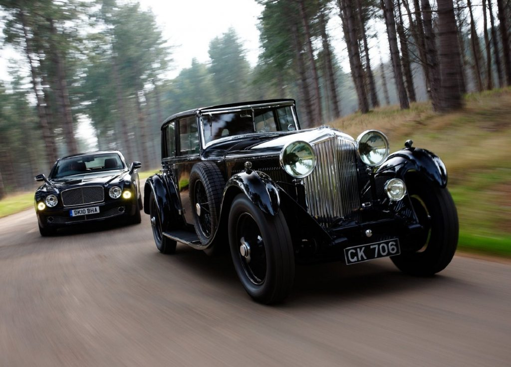 A black 1930 Bentley 8 Litre in front of a 2011 Bentley Mulsanne on a forest road
